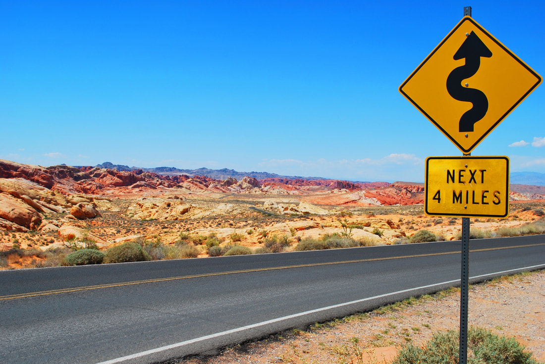 Desert road with caution sign